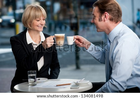 New corporate partners toasting coffee at cafe after finalizing business deal. - stock photo