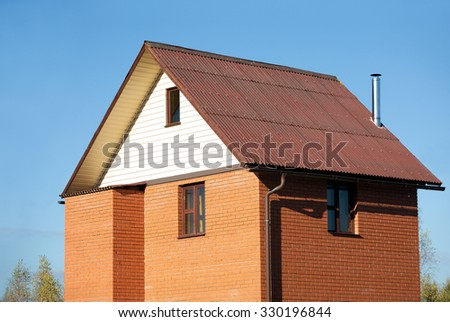 New country house of red brick, brown roof covered and siding on the front and a metal chimney - stock photo