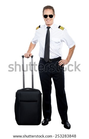 New day and new destination. Confident male pilot in uniform leaning hand on his suitcase and smiling while being isolated on white background - stock photo