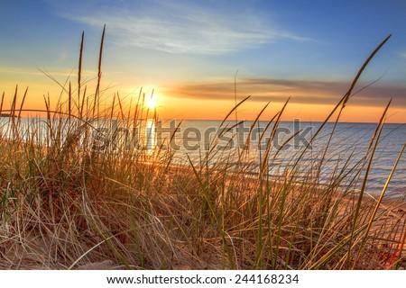 New Day Dawns. The sunrises over the horizon, illuminating the dune grass and beach. - stock photo