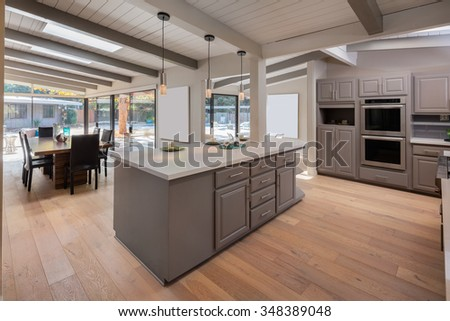 New decorated grey Kitchen in luxury home with marble counter top, kitchen island, dining area with table and chairs. - stock photo