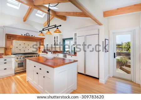 New decorated white Kitchen in luxury home with amazing wooden counter top, kitchen island, wooden floor and door with glass window leading to patio. Kitchen with dramatic wood beamed ceiling.  - stock photo