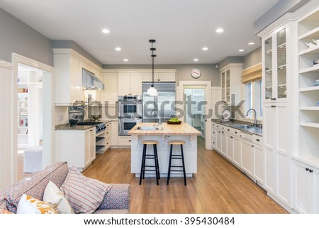New decorated white large Kitchen in luxury home with new wooden counter top, kitchen island, modern stainless steel integral gas oven, walk in storage unit / Kitchen Pantry and extractor fan. - stock photo