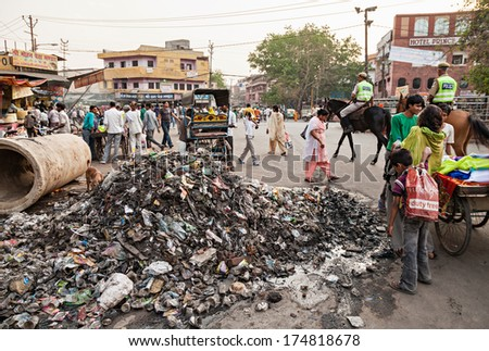 NEW DELHI, INDIA - APRIL 10: Big garbage heap and unidentified people on the street on March 27, 2012, New Delhi, India. India is a very dirty country. - stock photo
