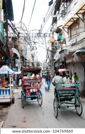 NEW DELHI, INDIA - AUGUST 14: Unidentified rickshaws ride on a narrow street in oldest part of the city on August 14, 2011 in New Delhi, India. Rickshaws is a  widespread transportation in India. - stock photo