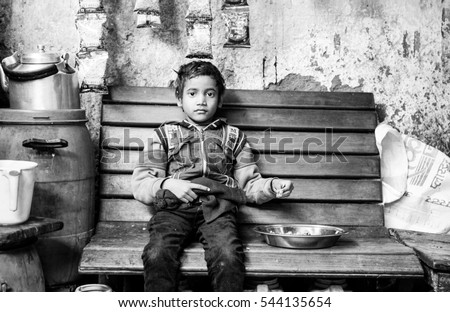 NEW DELHI, INDIA - DECEMBER 26, 2016: A Black and white portrait of a child sitting on a wooden bench with some food.