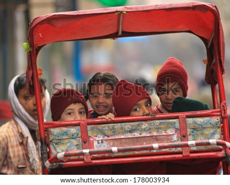 NEW DELHI, INDIA � FEBRUARY 24: School children wait to be taken to school in street cycle rickshaw outside Jama Masjid Mosque on February 24, 2013 in New Delhi, National Capital Region, North India - stock photo