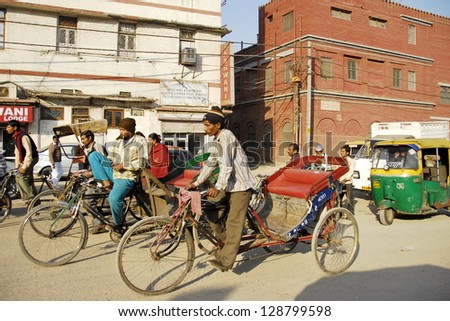 NEW DELHI, INDIA - FEBRUARY 4: Unidentified rickshaw men in a busy Indian street on February 4, 2010 in New Delhi, India. For many of Indians men cycle rickshaw is only way to make 2-3 US $ per day. - stock photo