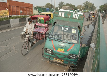 NEW DELHI, INDIA - MARCH 12: Unidentified Indian driver sleeps in the cabin of his truck on a bridge in Delhi, India on March 12, 2014. New Delhi is the busiest city in Asia with unregulated traffic. - stock photo