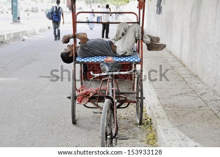 NEW DELHI, INDIA - MAY 23: Unidentified rickshaw man rests on his rikshaw in strange pose on May 23, 2009 in Delhi, India. For many of Indians men cycle rickshaw is only way to earn 2-3 US $ per day. - stock photo