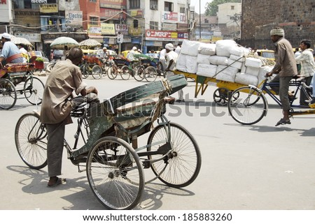 NEW DELHI, INDIA - MAY 23: Unidentified rickshaw man waits his passengers on a street on May 23, 2009 in New Delhi, India. For many of Indian men cycle rickshaw is only way to make 2-3 US $ per day. - stock photo