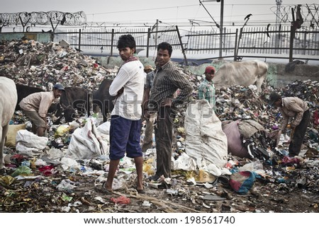 NEW DELHI, INDIA - NOVEMBER 6: Big garbage heap and unidentified people on the street on November 6, 2014, New Delhi, India.   - stock photo