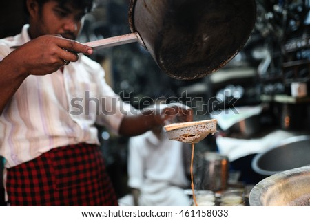 New Delhi, India - November 8, 2015 - Men pours cup hot milk tea Indian style or chai for customers in his shop along the street