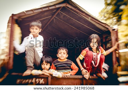 NEW DELHI, INDIA  NOVEMBER 16: Unidentified children of poor family in large car at the on November 16, 2013 in New Delhi, National Capital Region, North India  - stock photo