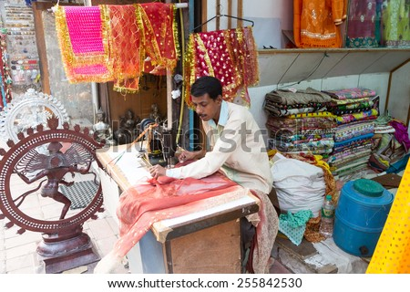 New Delhi, India - October 6 2013: An Indian craftman works on a sari, a traditional cloth for women, in front of the shop in the streets of New Delhi, India capital city. - stock photo