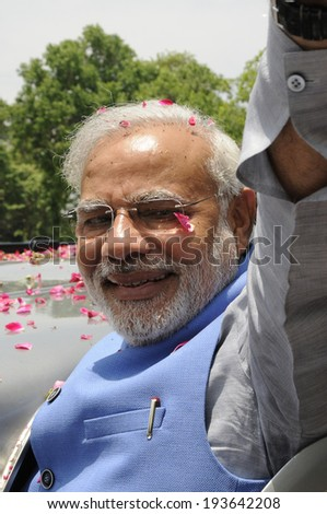 NEW DELHI-MAY 17: Indian Prime Minister Narendra Modi waiving towards the crowd during a roadshow  after wining the Indian National election on May 17, 2014 in New Delhi , India. - stock photo