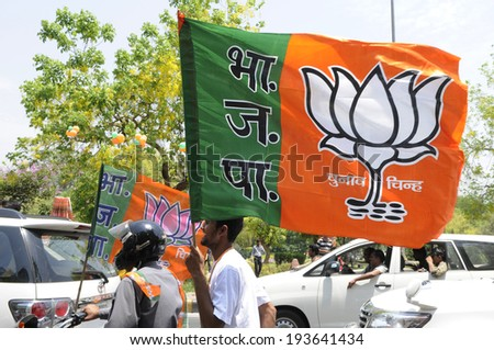 NEW DELHI-MAY 17: Supporters carrying a BJP flag on motorbike after wining the Indian National election on May 17, 2014 in New Delhi , India.  - stock photo