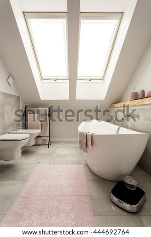 New design attic bathroom with big window, bathtub, toilet and bidet
