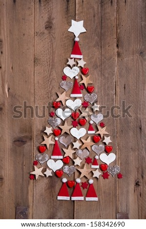 New design for a christmas tree - red and white decoration for xmas on a wooden brown background - stock photo