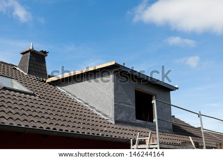 New dormer and scaffolding structure at the construction site - stock photo