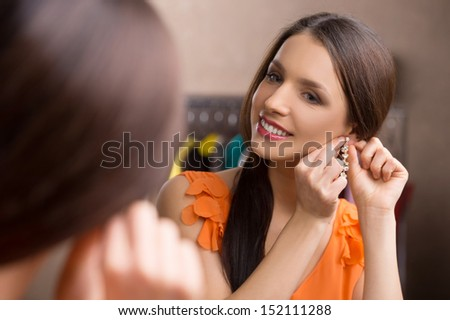 New earrings. Beautiful young woman putting on her new earrings and smiling while looking at the mirror - stock photo