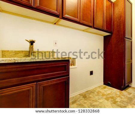 New empty laundry room with wood cabinets, sink and tile floor. - stock photo