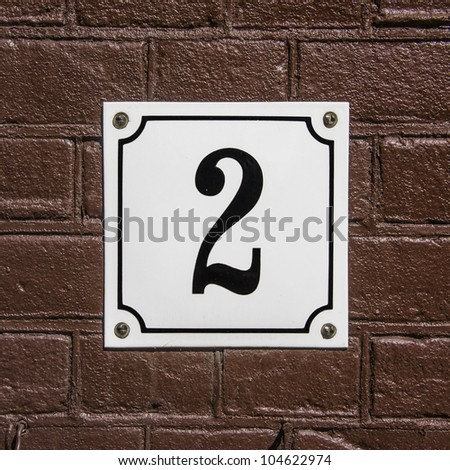new enameled house number two on a white plate attached against a brown painted wall - stock photo