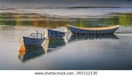 New England wooden Dory rowboats floating serenely in Kenneybunkport, Maine, USA - stock photo