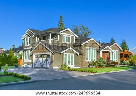 New family house in sunset light.  New house with paved driveway on blue sky background - stock photo