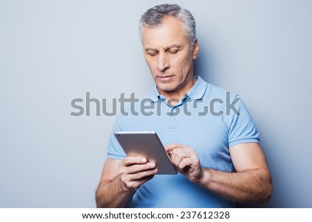 New gadget ? the best assistant. Confident senior man working on his digital tablet while standing against grey background - stock photo