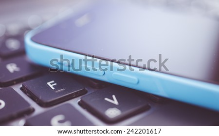 new generation smart phone lying on the computer keyboard