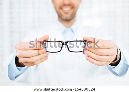 New glasses. Closeup of optician, optometrist giving eyeglasses to try - stock photo