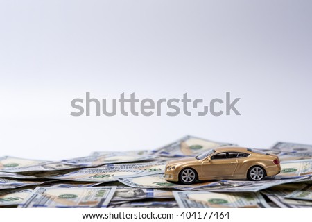 New golden toy car on the heap of dollars - stock photo