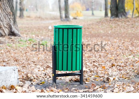 New green trash bin in the park in autumn - stock photo