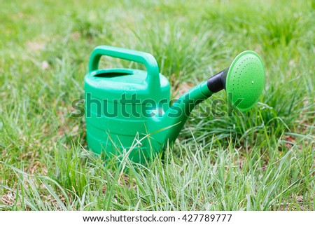 New green watering can standing on grass, spring concept