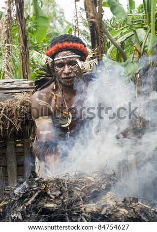 NEW GUINEA, INDONESIA -DECEMBER 28: The warrior of a Papuan tribe in traditional clothes and coloring in New Guinea Island, Indonesia on December 28, 2010 - stock photo