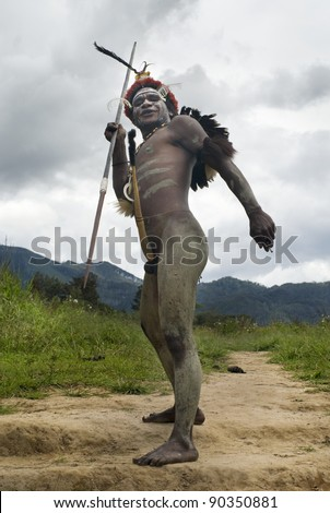 NEW GUINEA, INDONESIA -DECEMBER 28: Unidentified warrior of a Papuan tribe in traditional clothes is having a demonstration of war skills in New Guinea Island, Indonesia on December 28, 2010 - stock photo