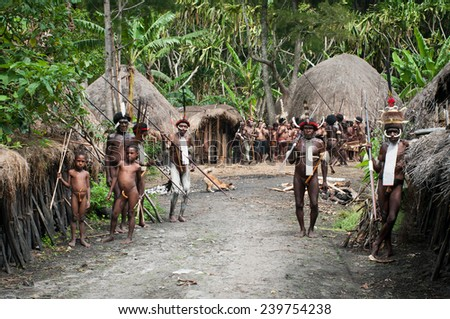 NEW GUINEA, INDONESIA -DECEMBER 28: Unidentified warriors of a Papuan tribe in traditional clothes are having a demonstration of war skills in New Guinea Island, Indonesia on December 28, 2010  - stock photo