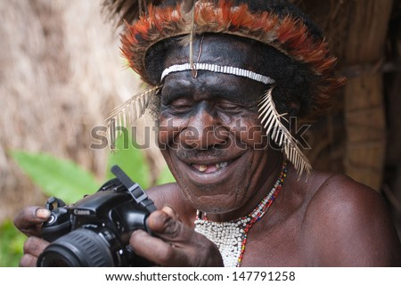 NEW GUINEA, INDONESIA - JANUARY 07: Papuan in traditional clothes and coloring in New Guinea Island, Indonesia on January 07, 2009 - stock photo