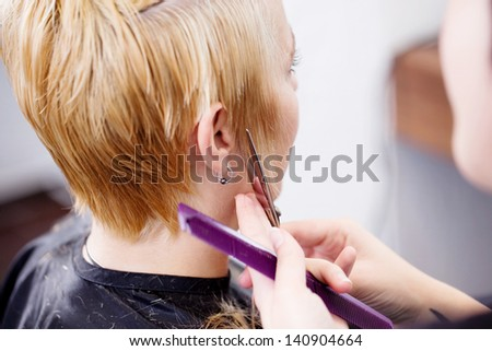 new haircut for blond woman in salon - stock photo