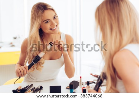 New hairstyle for today! Beautiful young womanlooking at her reflection in mirrorand using her curling iron while sitting at the dressing table