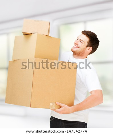 new home and post delivery concept - young man carrying carton boxes