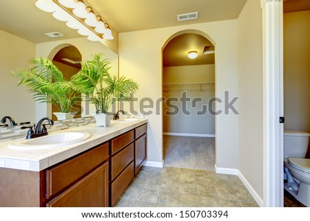 New home bathroom  interior with shower and bath combination, wood cabinet and toilet. - stock photo