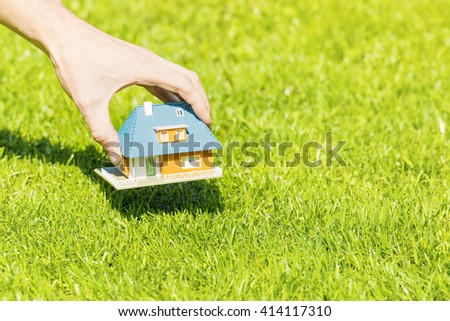 new home concept, hand putting house scale model on grass - stock photo