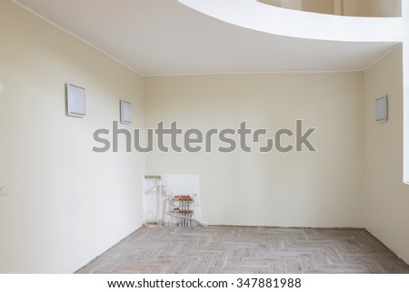 New home construction interior living room with unfinished tile wooden floors and balcony. The heating system also are partially unfinished. - stock photo