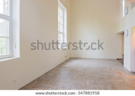 New home construction interior living room with unfinished tile wooden floors, big windows and balcony.  - stock photo