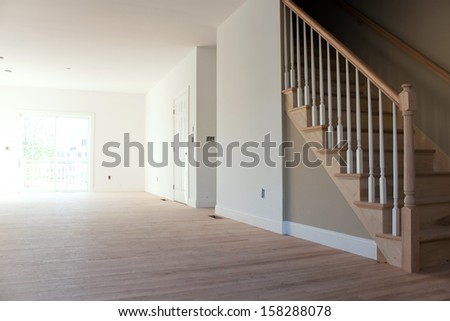 New home construction interior room with unfinished wood floors stairway and railings. Electrical and hvac connections also are partially unfinished. - stock photo