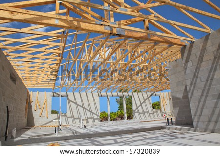New home Construction of a cement block home with wooden roof trusses view from inside.