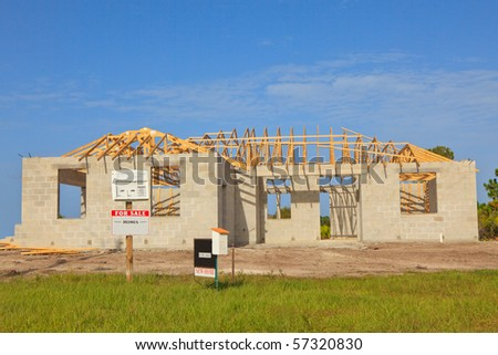 New home Construction of a cement block home with wooden roof trusses view from outside with a for sale sign in front. - stock photo