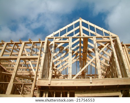 New home construction with wooden house frame - stock photo